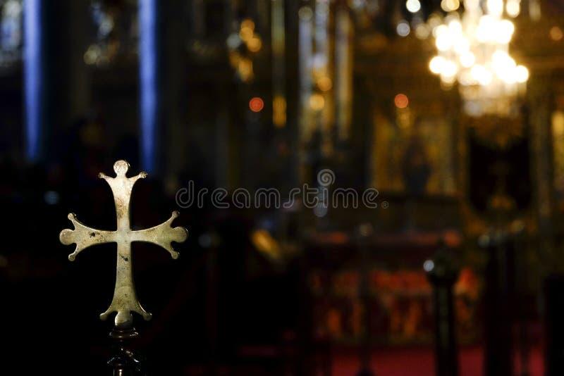 Metalliskt guld- rundat kors inom en kyrka arkivbilder