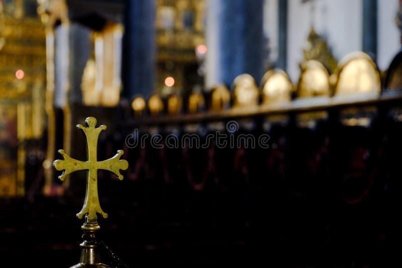 Metalliskt guld- rundat kors inom en kyrka royaltyfria foton