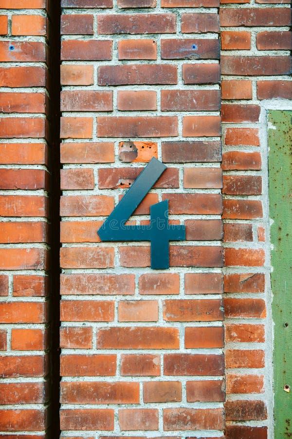 Metalliskt nummer fyra på en tappningtegelstenvägg arkivbild