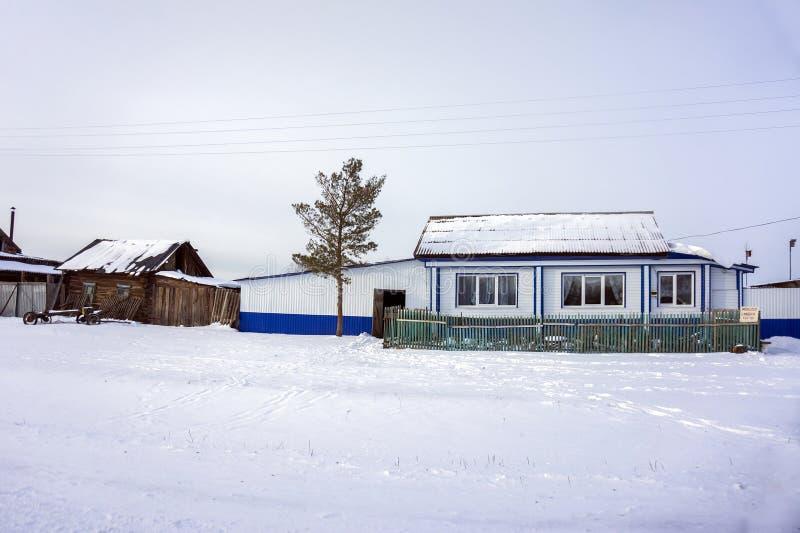 Metalliskt skydd av trähuset i en liten Siberian by i vintersäsongen arkivbilder