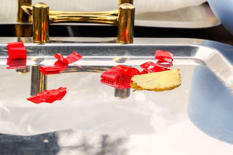 Metallkökmagasinet med gulinghandtag smyckade med röda band med ett stupat gult höstblad Märkes- workpiece royaltyfri fotografi
