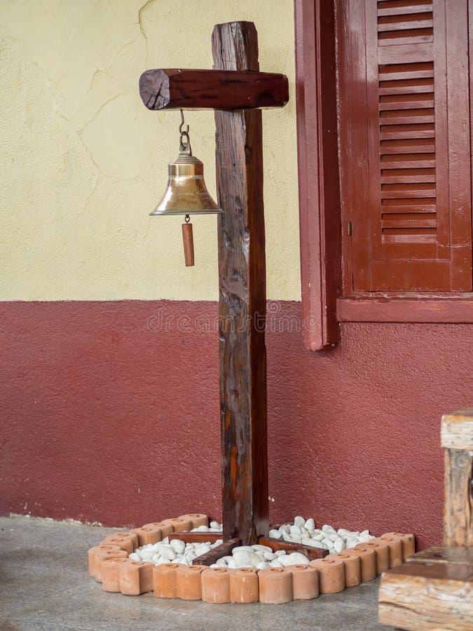 Metallklocka som hänger på den wood ställningen på drevstationen royaltyfria foton