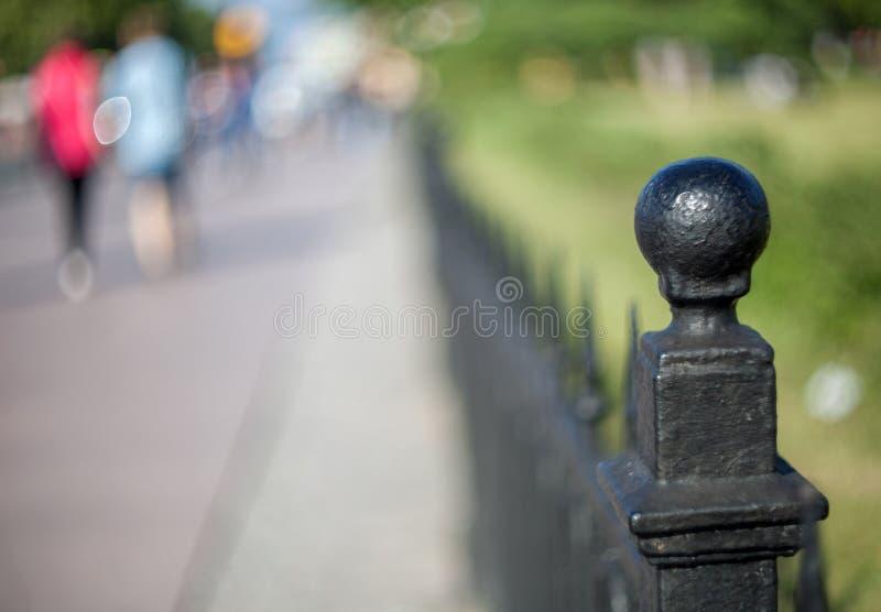 Metallknauf in Form eines Balls auf dem Gusseisenzaun des künstlerischen Castings in einem Park in St Petersburg mit verwischt lizenzfreies stockfoto