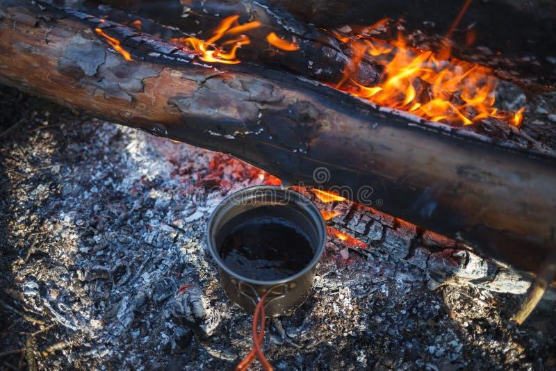 Metallkoppen med te värmas från lägerelden i vinter arkivfoto