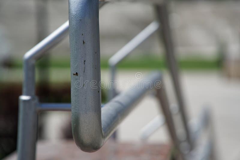 Metallledstänger på att korsa vägen, närbild, skuggor arkivbild