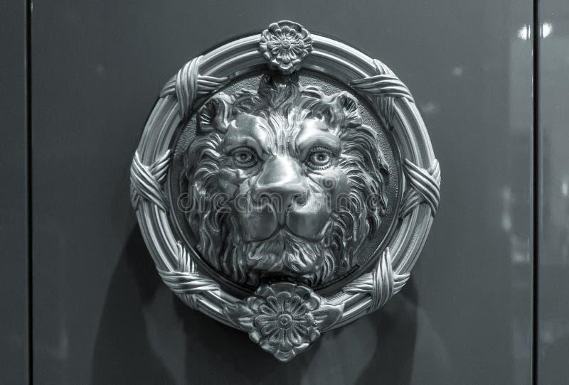Metalllejonhuvud på dörren arkivfoto