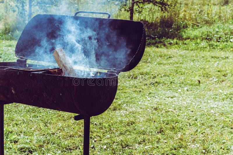 Metallmessingarbeiter mit Feuer und Rauch am sonnigen Sommerhintergrund Vorbereitung der Holzkohle vom Holz für einen shish Grill lizenzfreie stockfotos