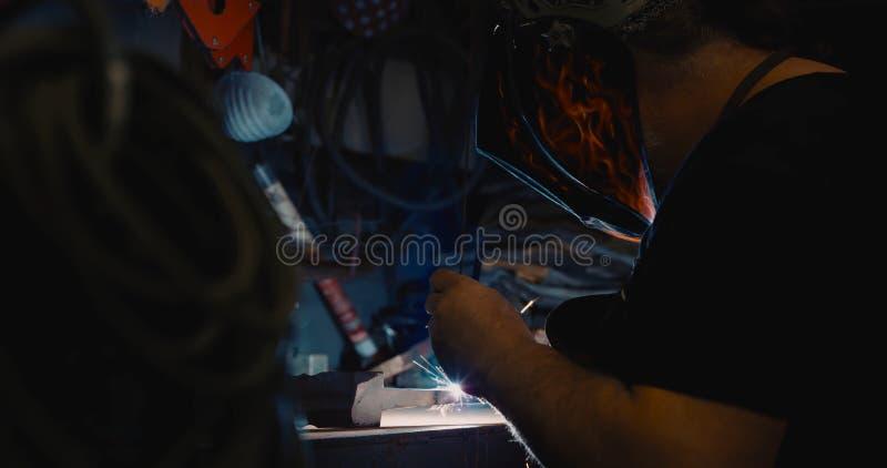 Metallo di saldatura del saldatore in officina con le scintille immagini stock