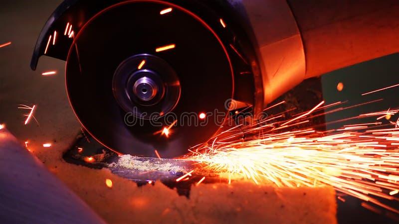 Metallo di taglio con la smerigliatrice di disco con le scintille luminose fotografia stock