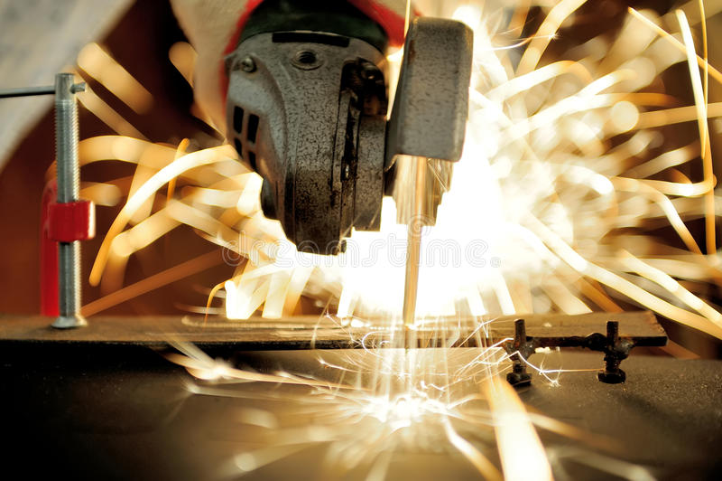Metallo di taglio del lavoratore con la smerigliatrice immagini stock libere da diritti