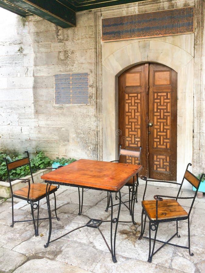 Metallo e tavola di legno con due sedie arabe di stile davanti a fotografia stock