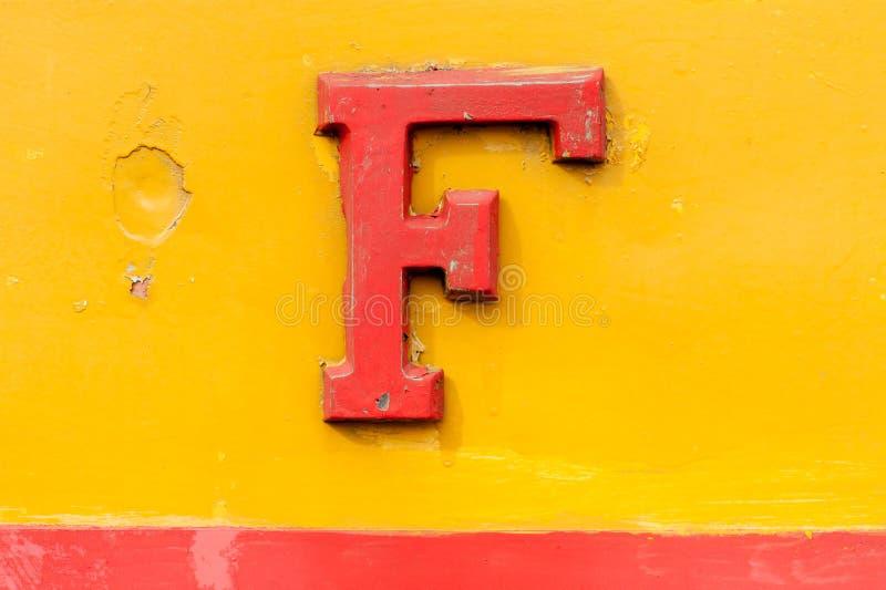 Metallo impresso annata F rossa sopra giallo immagine stock