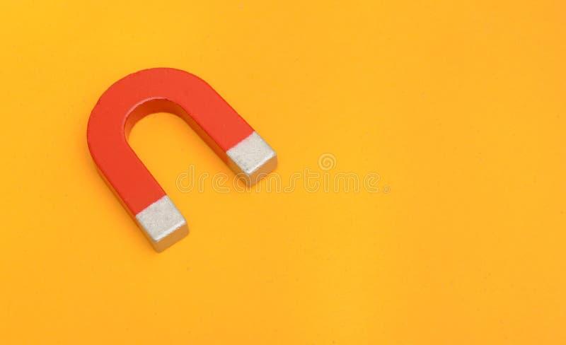Metallo rosso del magnete sul concetto giallo di istruzione del fondo immagini stock libere da diritti