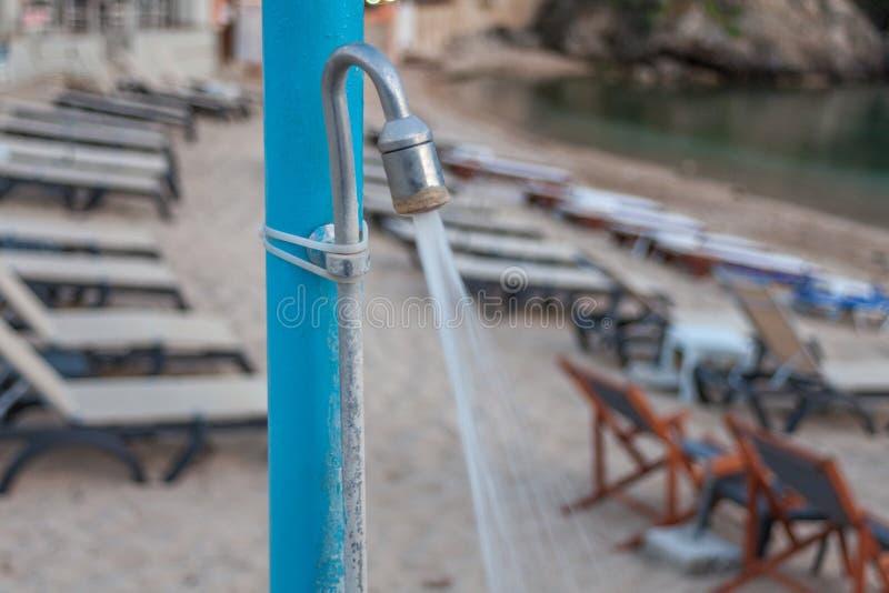 Metallpfosten mit einem undeutlichen Hintergrund Wasser, das vom Duschkopf fließt Druckerhöhung stark im Rohr Strandurlaubsort am stockfoto