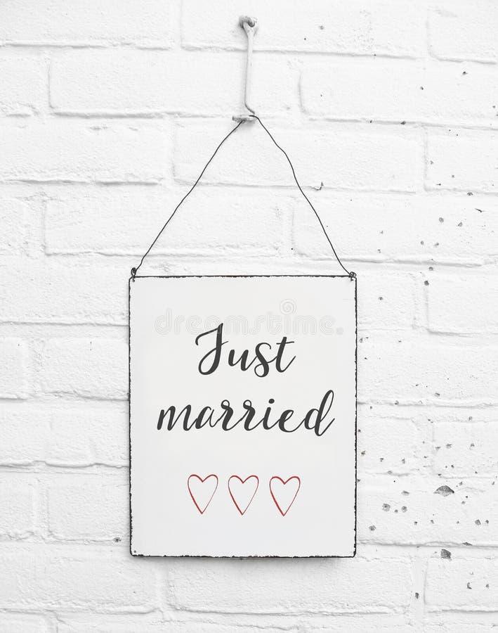 Metallplatte des weißen Quadrats auf weißem Ziegelsteinhintergrund - mit Text heiratete gerade für Liebespaare und -Hochzeiten stockbild