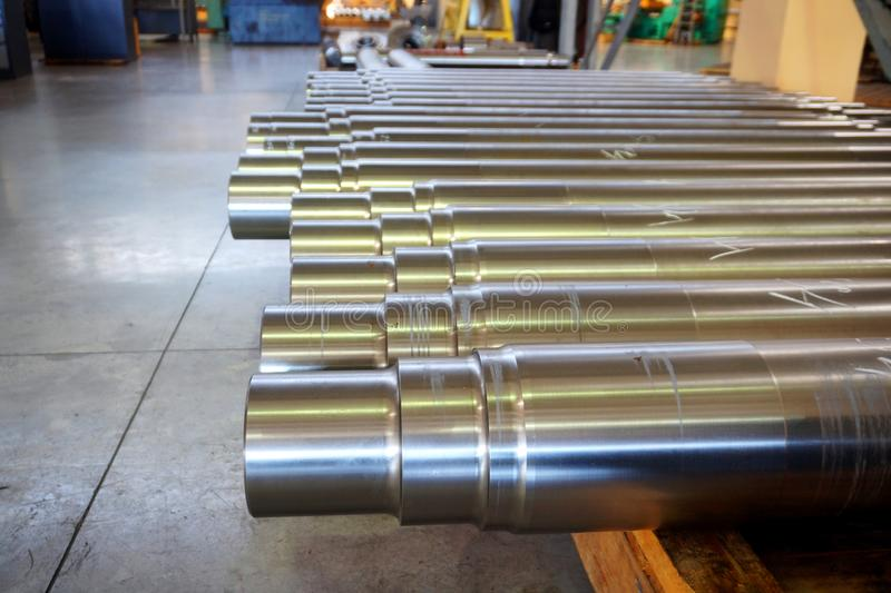 Metallprodukter i lagret, stora runda axlar ligger på en träkugge i fabriken i shoppa royaltyfria foton