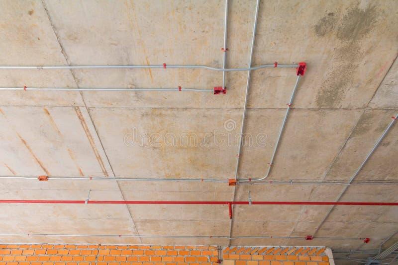 Metallrör i konstruktions- och brandspridare på det röda röret hänger från takinre royaltyfri foto
