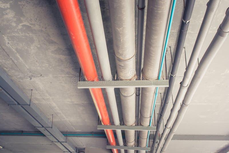 Metallrohrleitungssystem installieren auf Decke des konkreten Gebäudes stockbild