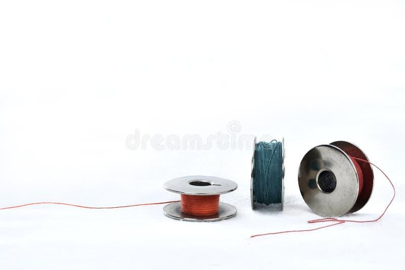 Metallrulle med kulöra trådar på vit bakgrund fotografering för bildbyråer