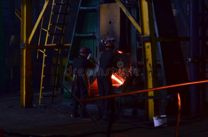 Metallschmieden, Geschäft schmiedend Hydraulischer Hammer formt das glühende Billet stockfotografie