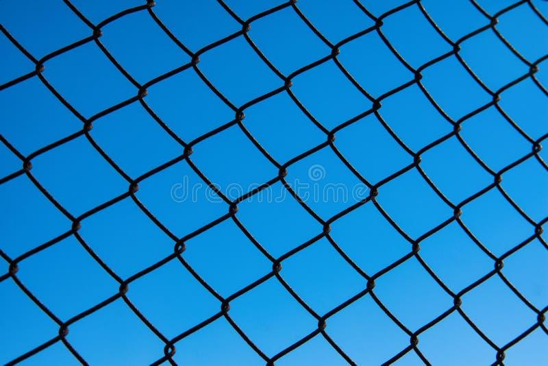 Metallschwarze Zaunmaschenfiletarbeit gegen einen klaren blauen Himmel lizenzfreie stockbilder