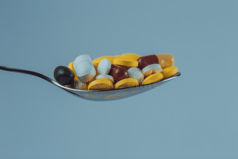 metallsked mycket av piller på en blå bakgrund, närbild arkivbilder