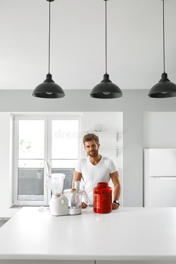 metallskivstånger med rött sugrör Sund man som går att förbereda skakan i kök royaltyfri fotografi