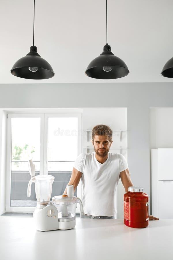 metallskivstånger med rött sugrör Sund man som går att förbereda skakan i kök royaltyfri bild