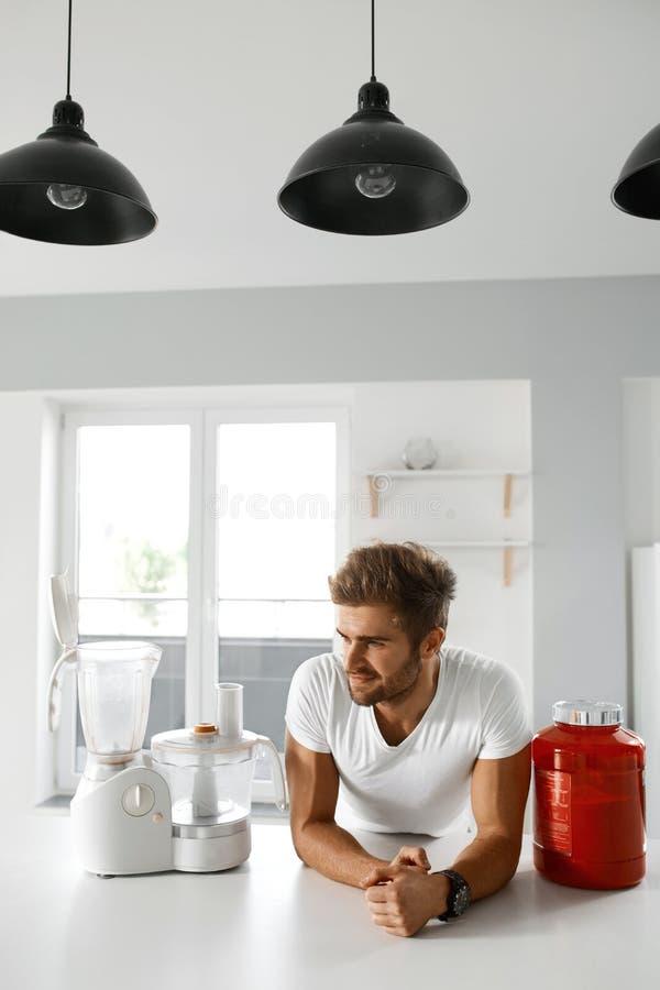 metallskivstånger med rött sugrör Sund man som går att förbereda skakan i kök fotografering för bildbyråer