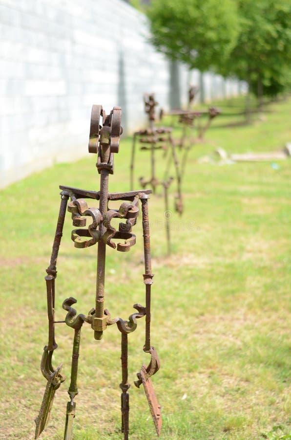 Metallskulptur von den menschlichen Figuren, die in Linie marschieren stockbild