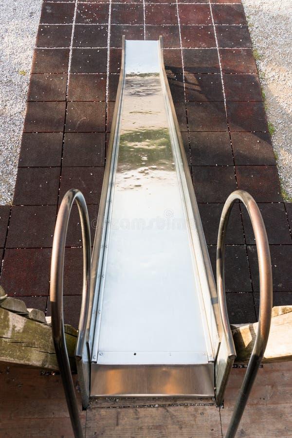 Metallspielplatzdia, das unten auf einen roten Mattenboden geht lizenzfreie stockbilder