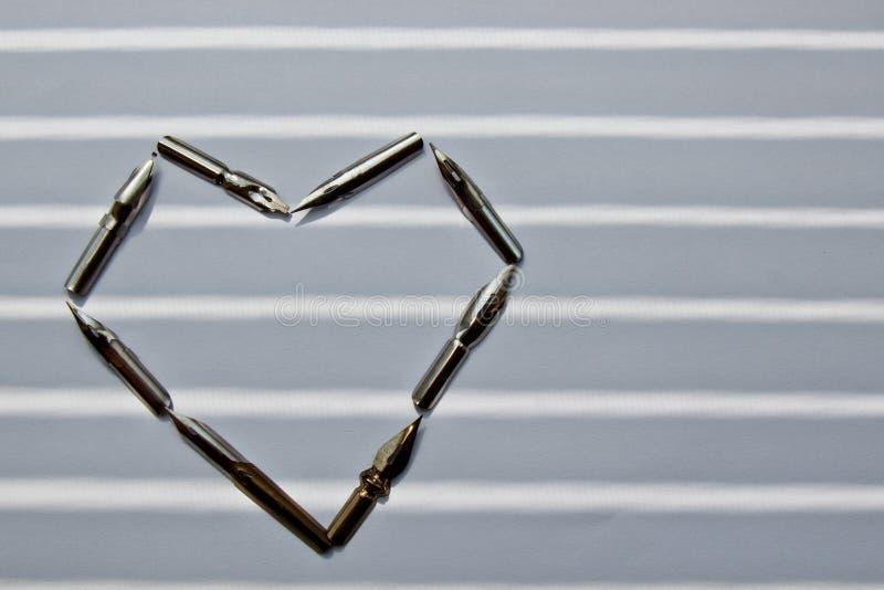 Metallspitzen f?r den Tintenstift auf einem wei?en Hintergrund in den Solarstrahlen Briefpapier auf wei?em Schreibtischabschlu? h lizenzfreie stockfotografie