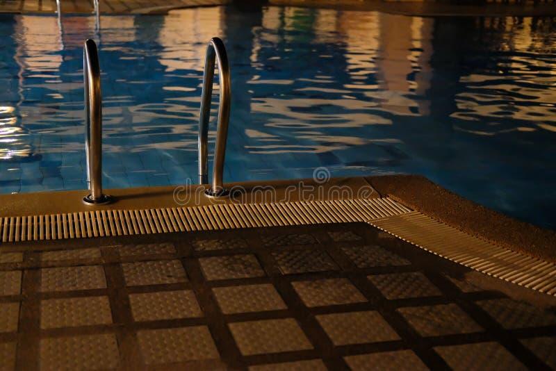 Metallstahlgriff an Rand Poolside des Swimmingpools im Hotel nachts lizenzfreie stockfotografie