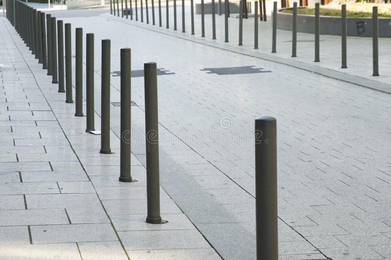 Metallstolpar som gräns av en gata arkivbild