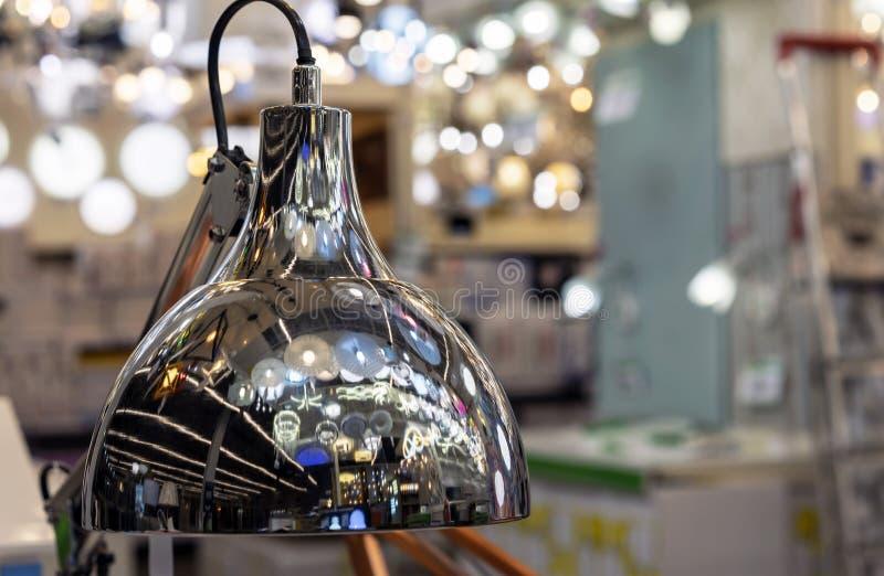 Metalltabelllampa med reflexionen av en variation av ljuskronor royaltyfria foton