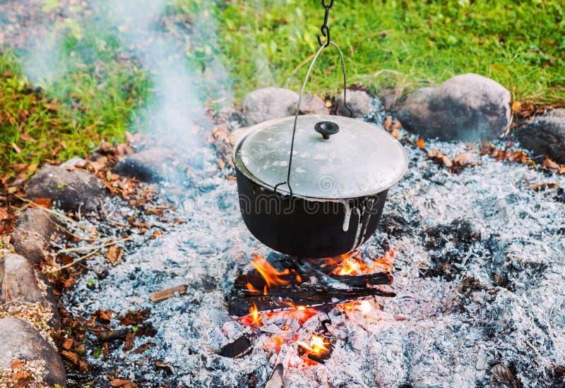Metalltopf über einem Lagerfeuer draußen lizenzfreie stockfotografie