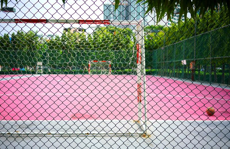 Metalltrådstaketet eller tråd kopplar ihop grönt stål med suddighetsfotboll eller rosa Futsal sportar som däckar bakgrund royaltyfri bild
