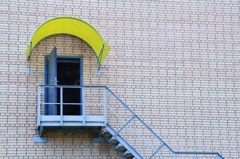 Metalltrappuppgång och en öppen dörr på en tegelstenvägg av huset arkivbild