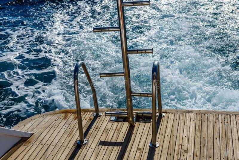 Metalltrappuppgången för nedstigning in i vattnet och vågen spårar med vitt skum på en vattenyttersida bakom av den snabba rörand arkivbild