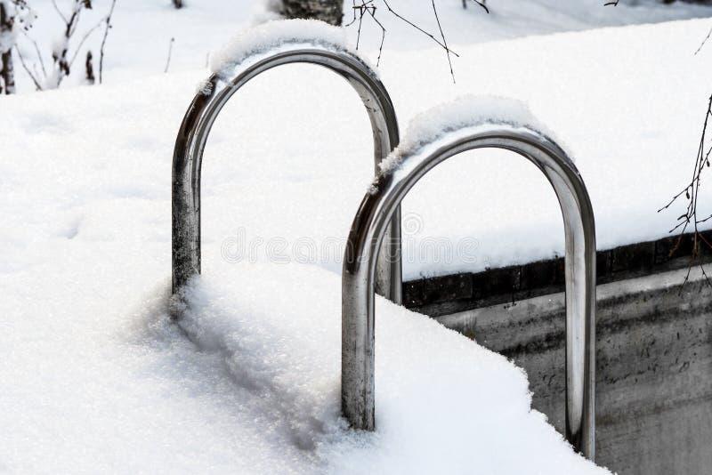 Metalltreppenhaus im Pool im Freien bedeckt mit Schnee stockbilder