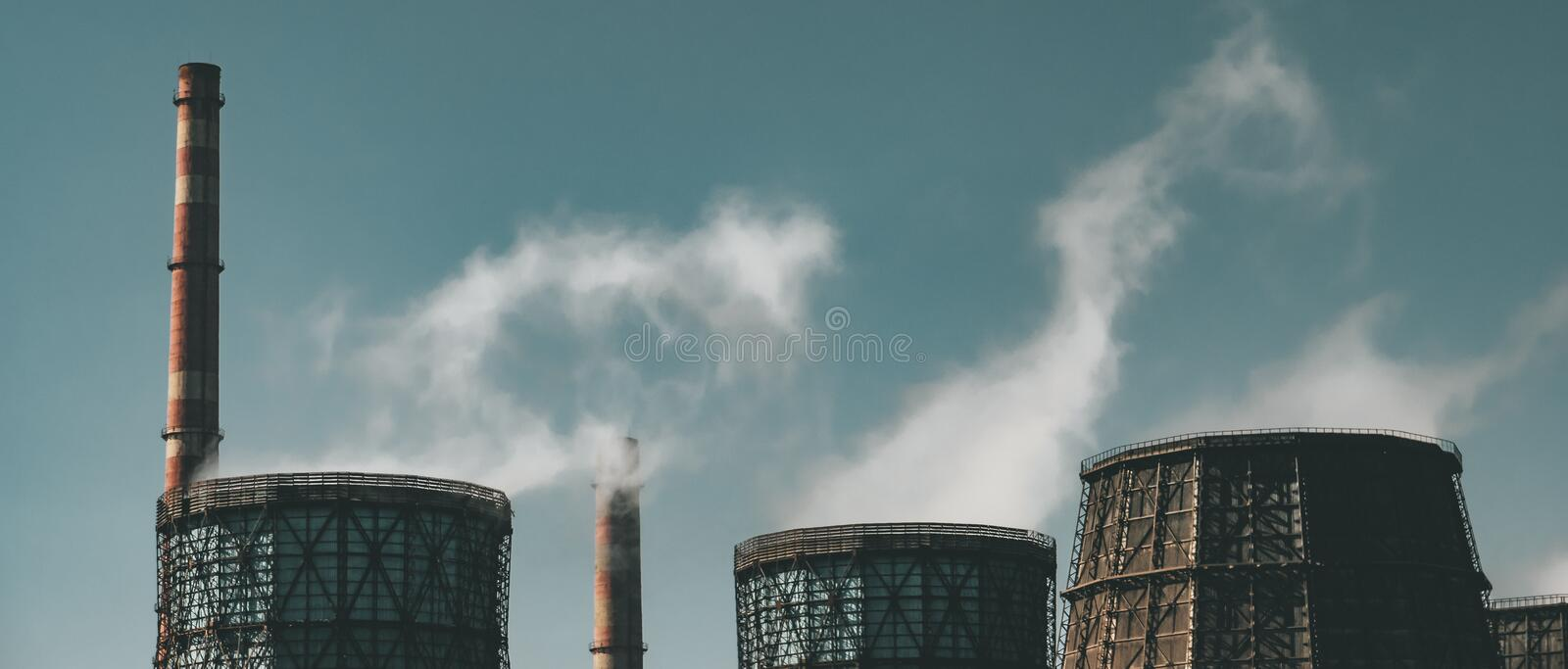 Metallurgical factory with chimneys and smog. Pollution and industry background, panoramic image.  royalty free stock photography