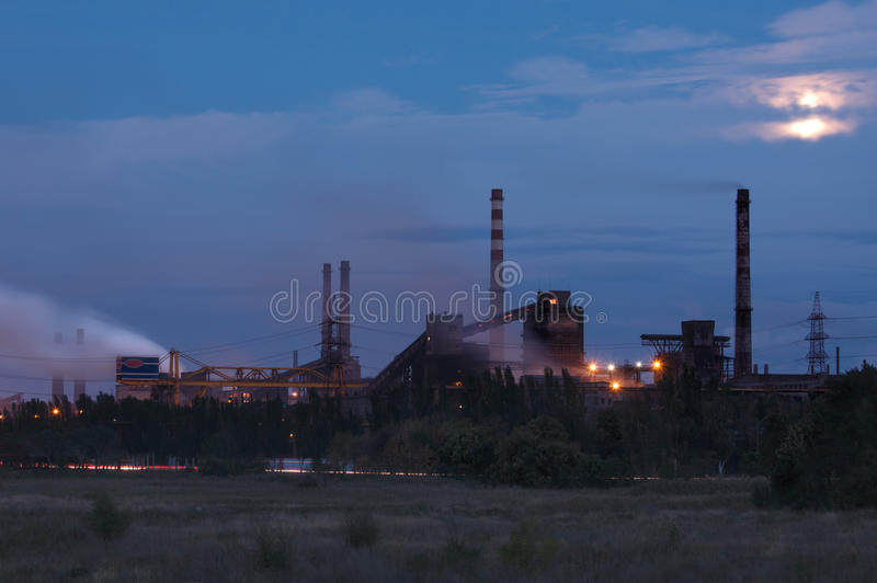 Metallurgical factory with smoke stack. At night stock photography