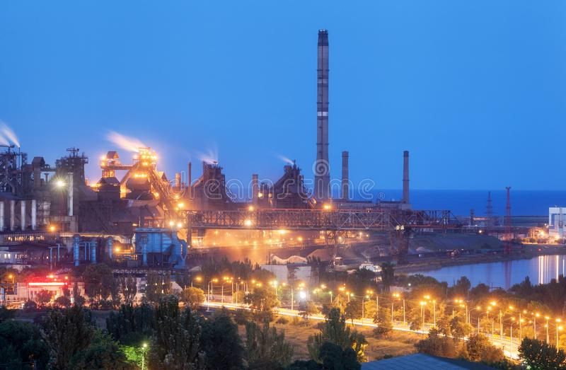 Metallurgical plant at night. Steel factory with smokestacks royalty free stock photo