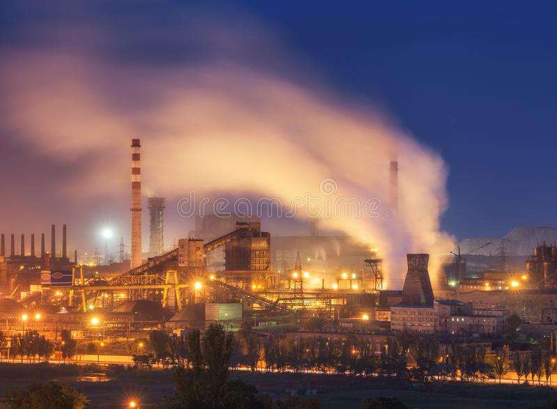Metallurgical plant at night. Steel factory with smokestacks stock photo