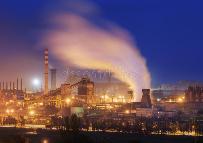 Metallurgical plant at night. Steel factory with smokestacks. Steelworks, iron works. Heavy industry in Europe. Air pollution from smokestacks, ecology stock photography