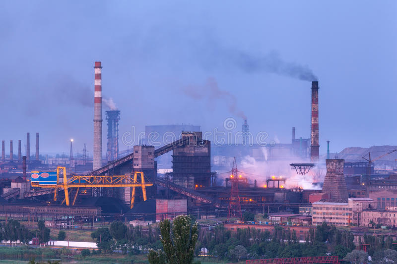 Metallurgical plant at night. Steel factory with smokestacks. Steelworks, iron works. Heavy industry at twilight. Air pollution from smokestacks, ecology stock image