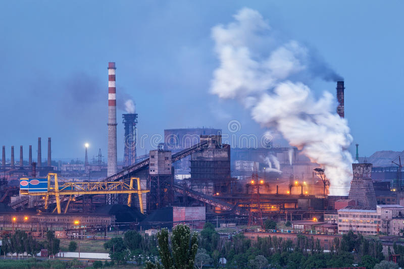 Metallurgical plant with white smoke at night. Steel factory with smokestacks . Steelworks, iron works. Heavy industry. Air pollution from smokestacks, ecology stock photos
