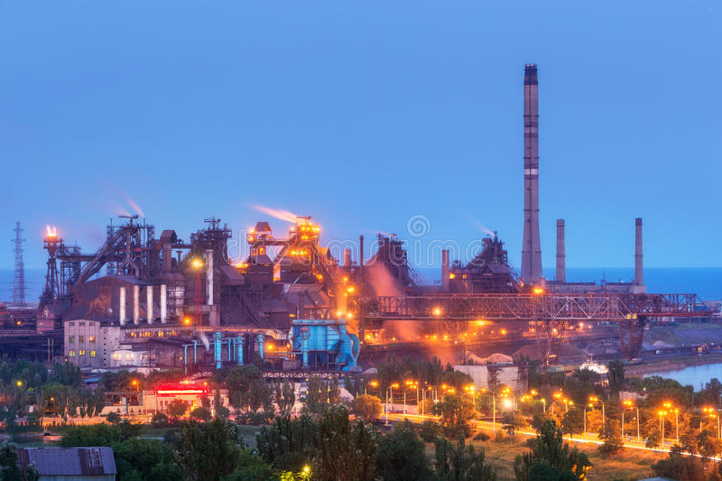 Metallurgical plant with white smoke at night. Steel factory with smokestacks . Steelworks, iron works. Heavy industry. Metallurgical plant at night. Steel stock photo