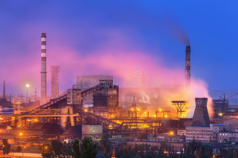 Metallurgical plant with white smoke at night. Steel factory with smokestacks . Steelworks, iron works. Heavy industry. Metallurgical plant at night. Steel royalty free stock photography