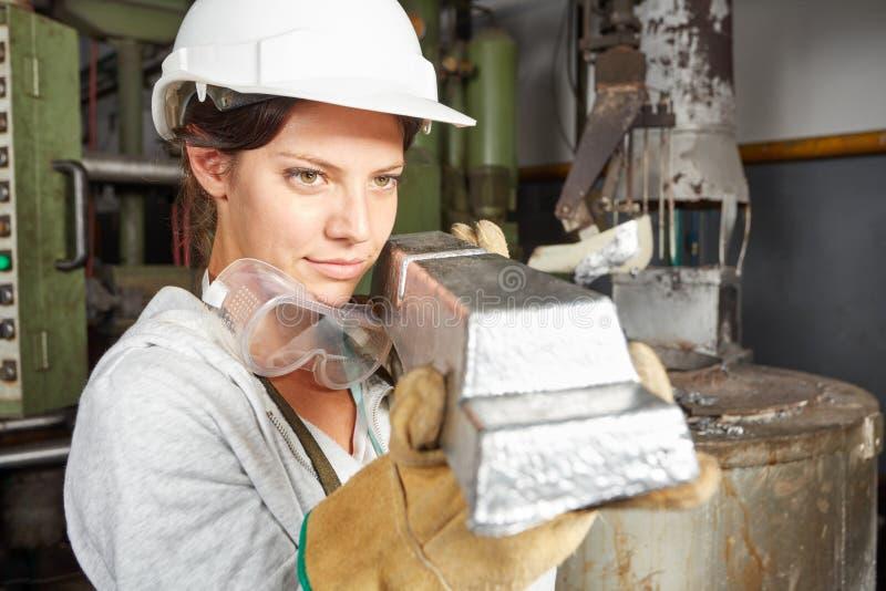 Metallurgiearbeitskraft, die Stahlwerkstück hält lizenzfreie stockfotografie